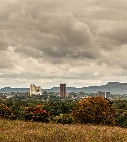 UMass Amherst from far away, showing leaves, fields and mountains