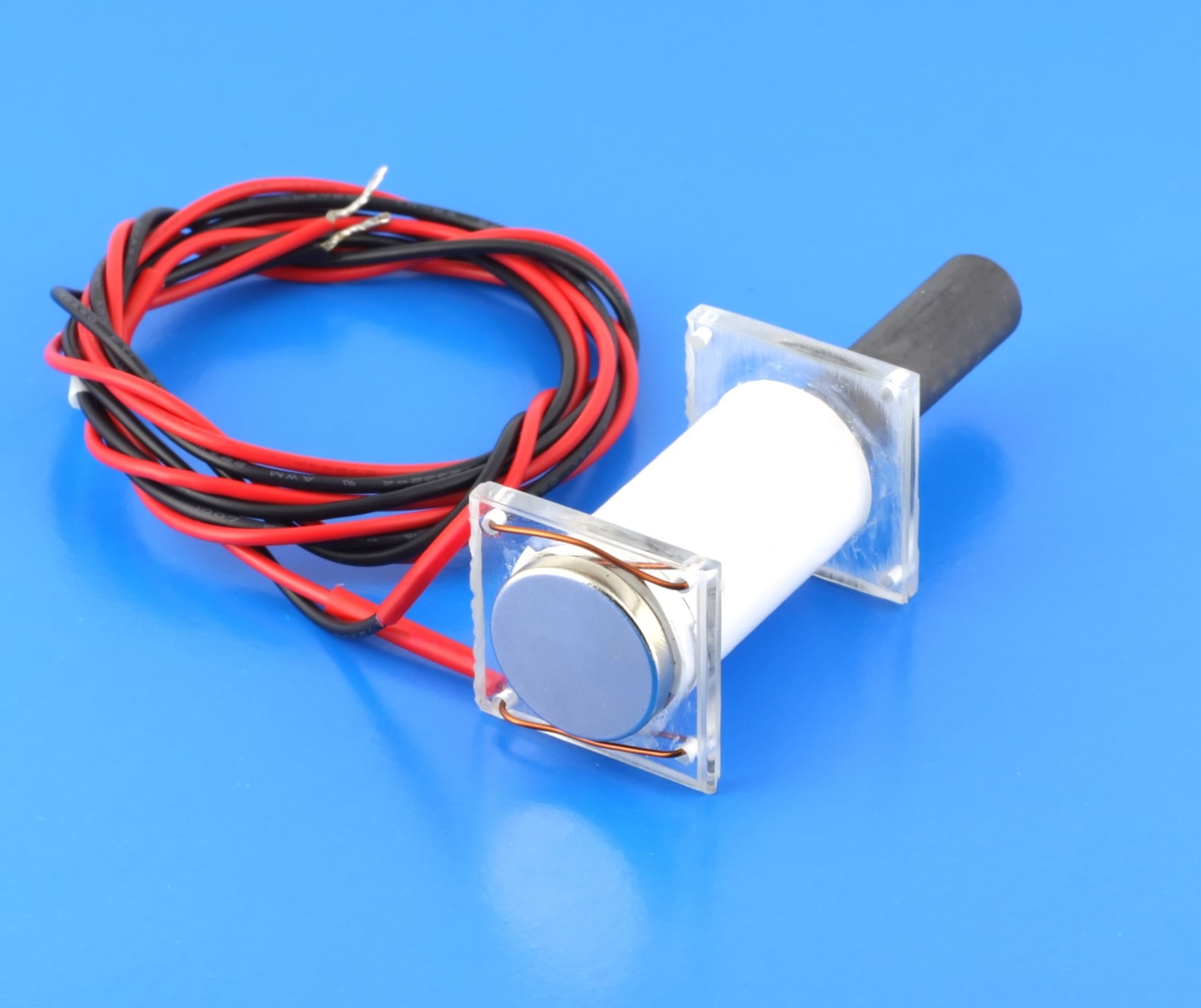 Image of a sensor on a blue table with black and red wires