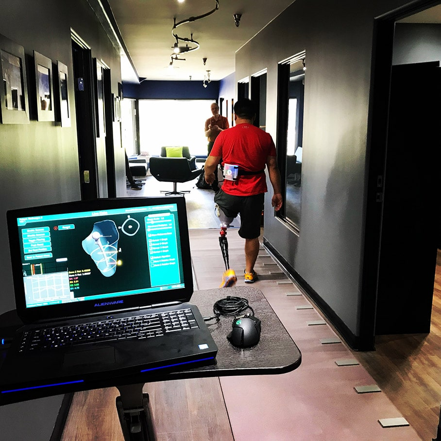 Image of a man walking down a hallway with a SoundFit Prosthetic